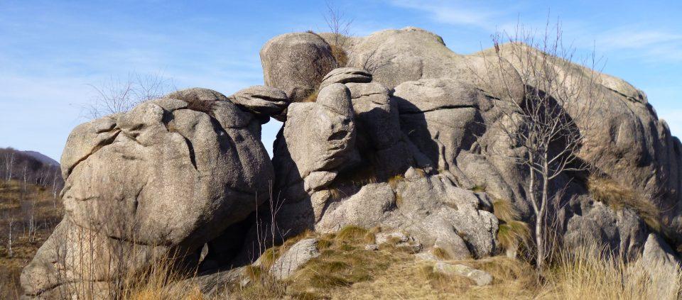 Grossa roccia in granito, arrotondata, su cresta erbosa.