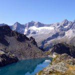 Lago alpino su un altopiano, di fronte a una valle e a monti sullo sfondo