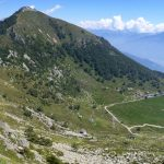 Verde alpeggio in una piana ai piedi di una cima isolata