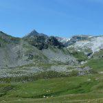 Piana con pascolo d'alta quota, sullo sfondo una cresta di monti.
