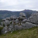 Cresta in roccia bianca, pare un muro, affacciata su una valle, sullo sfondo monti boscosi