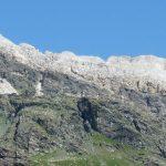 Cresta montuosa con parete grigia e cime bianche.