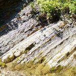 Roccia grigio scura con strati inclinati sottili..