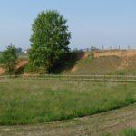 Ampio prato erboso, sulla destra una scarpata di terreno rosso