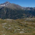 Altopiano erboso con rocce bianche e grige, sullo sfondo una cresta montuosa