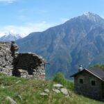 Vecchie baite alpine in pietra, sullo sfondo un'alta montagna