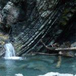 Gola di rocce a strati inclinati grigie e torrente dalle acque cristalline
